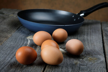 Still-life with eggs and a frying pan on boards photo
