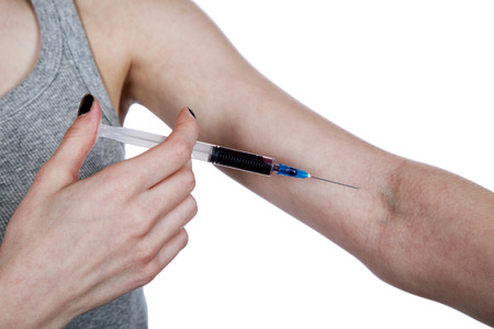 hand injecting arm with a syringe close up