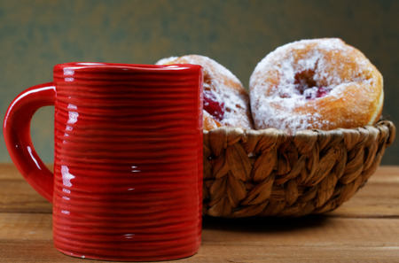 Red cup and fruitcakes in plates on a rural table