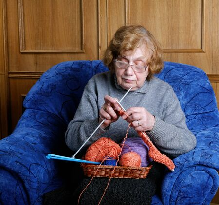 octogenarian: The old woman sits in an armchair and knits Stock Photo