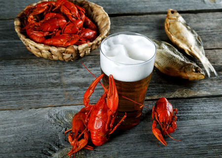 cancers: Tasty boiled crayfishes vyaleny fish and beer on old table Stock Photo