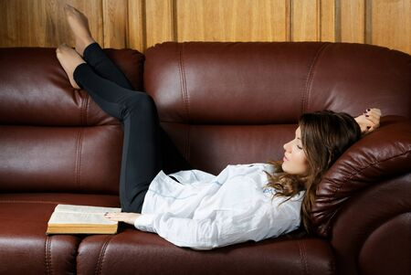 Sleeping girl with a book on the couch Stock Photo