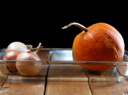 stillife: Small pumpkin and onions in a glass plate