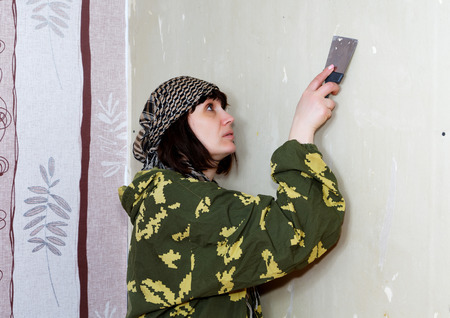 scraping: woman scraped the old wallpaper off the wall