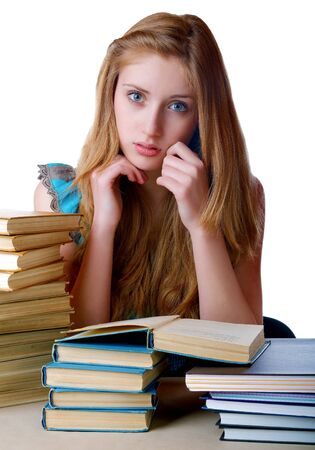 The girl with pile of books and writing-books on a white background photo
