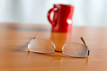 office life: Still life with glasses and a red cup Stock Photo