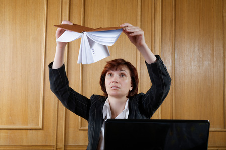 unmotivated: woman in the office shakes organizer
