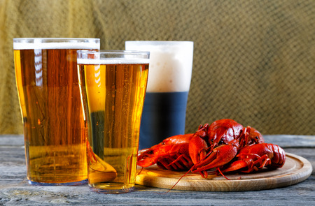 cancers: Tasty boiled crayfishes and beer on old table Stock Photo