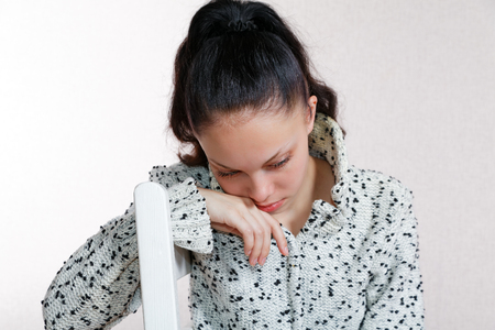 bowed head: she bowed her head sitting on a wooden chair