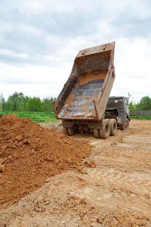 dumptruck: dump-body truck unloads a ground on the land