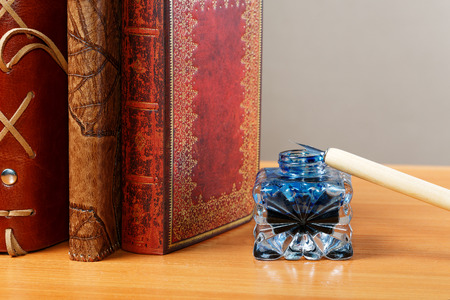 inkstand: Inkwell and pen against standing leather organizers Stock Photo