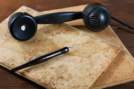 caligraphy: Still-life with old writing-books a nib and phone