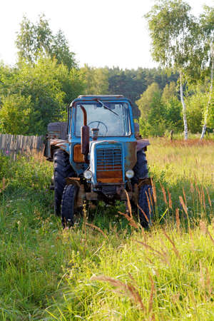 wheel tractor: Old wheel tractor with the trailer against wood