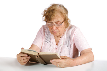 octogenarian: old woman in glasses reads the book on a white background