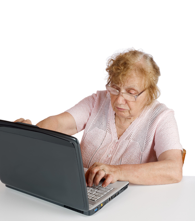octogenarian: granny in glasses looks at the screen notebook on a white background Stock Photo
