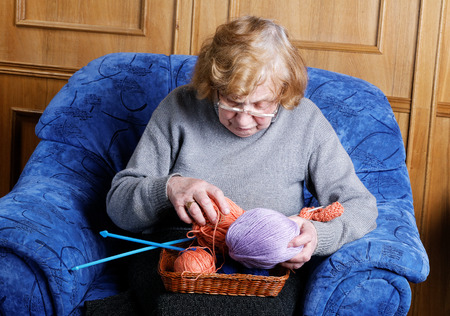 the great grandmother: grandmother in a chair with a thread for knitting Stock Photo