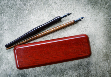 inkstand: vintage fountain pens, and pencil case on retro background