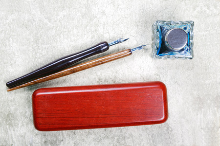 inkstand: vintage fountain pens and ink on a retro background