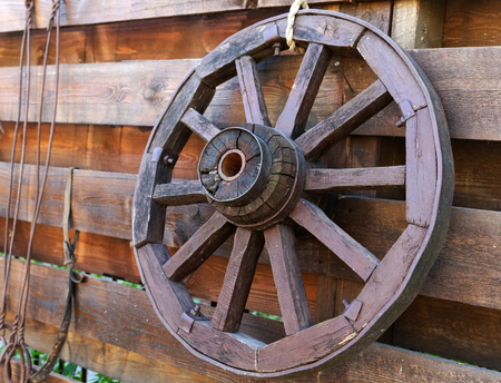 carreta madera: Rueda de carro de madera en la valla Foto de archivo