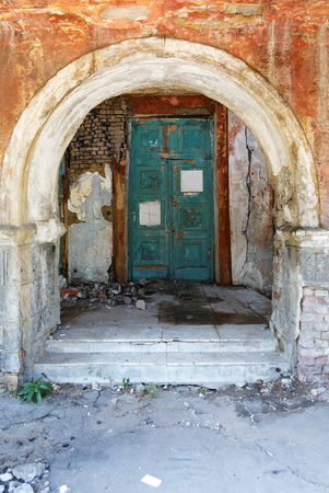 scabrous: old door and the arch in the crumbling building Stock Photo