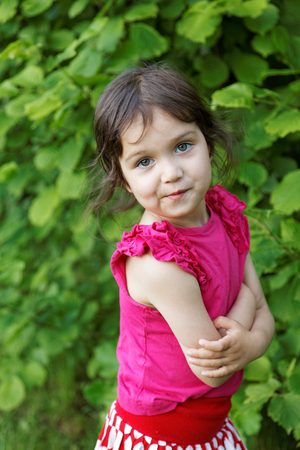 little girl grimacing on a background of green leaves Stock Photo