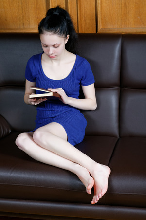 girl reading a book sitting on the couch Stock Photo