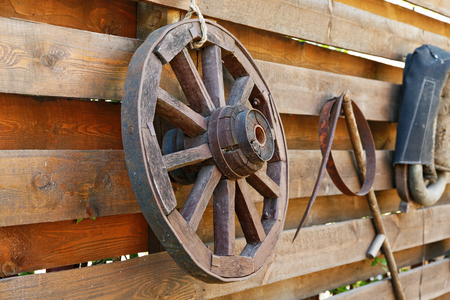wooden wagon wheel on the fence Stock Photo