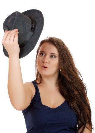 The girl looks surprised at the hat in her hand on a white background Stock Photo