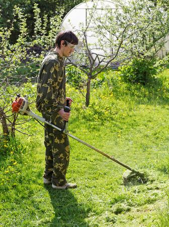 Man mows the grass in his garden Stock Photo