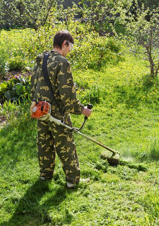 Man mows the grass in his garden summer day