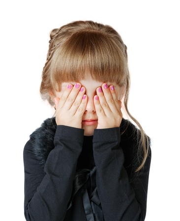 Little girl covers her face with hands on a white background