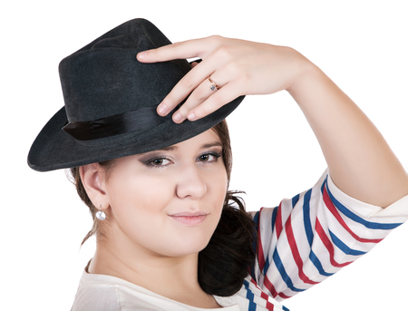 buxomy serious girl with a hat on a white background  Stock Photo