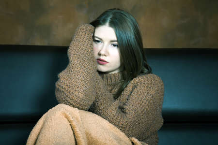 girl in a sweater sits on the couch wrapped up in a rug