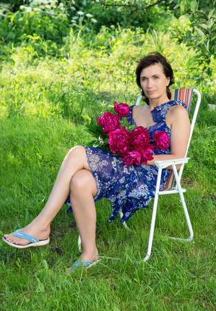 The woman of average years with flowers in a garden Stockfoto