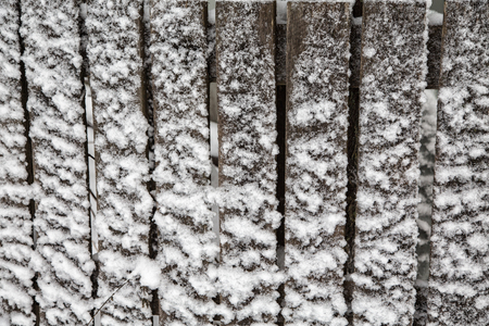 old wooden fence board covered with snow