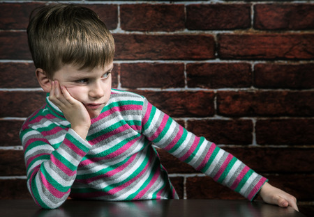 six year old boy with a thoughtful expression on the wall background