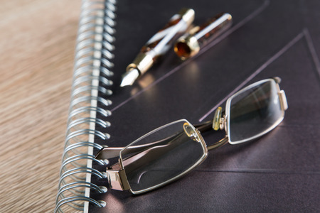 glasses fountain pens and diaries with leather cover