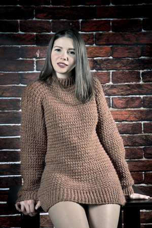 girl in sweater leans on coffee table on brick wall background