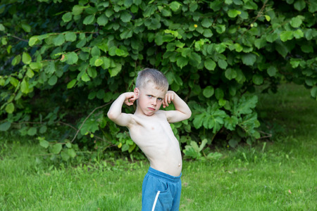 little boy shows biceps in the garden on a summer day