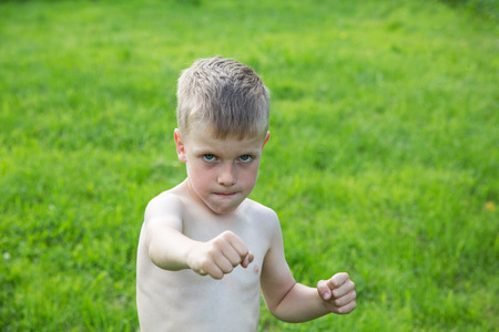little boy boxing on the lawn on a summer day