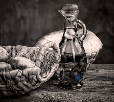 still life with olive oil and bread basket black and white Stock Photo