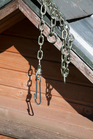 Chain for a dog hanging on a booth on a sunny day