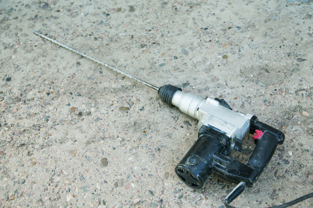 perforator with a long drill rests on a concrete surface Banco de Imagens