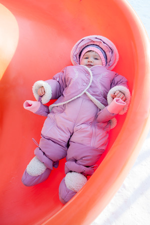 little girl rolling downhill on a winter day 写真素材