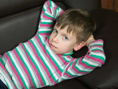 six year old boy lying on the couch and looking at the camera