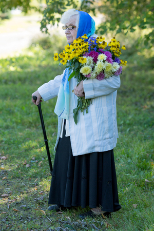 grandmother with a cane and flowers on the background of trees