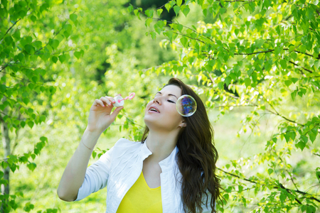 girl blows soap bubbles on the background of spring trees 写真素材