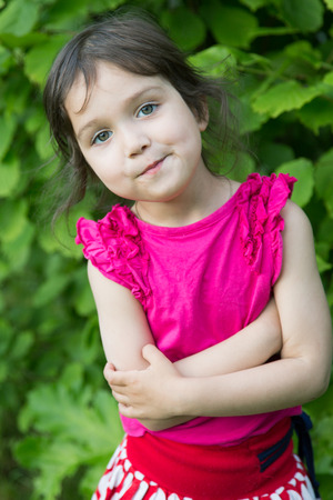 little girl grimaces against green foliage on a summer day