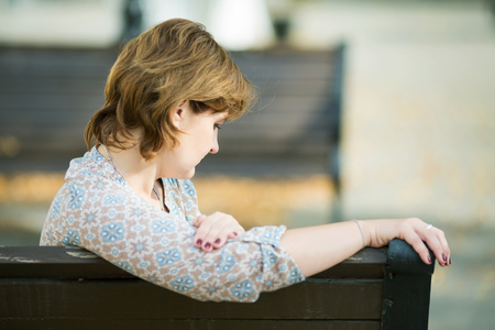 middle-aged woman sits on a bench in a public garden on a summer day