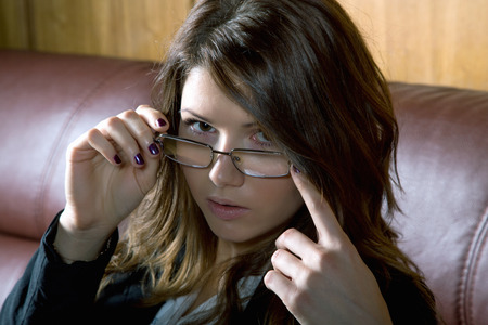 girl with glasses and a jacket on the sofa close-up 写真素材